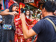 "04 FEBRUARY 2016 - BANGKOK, THAILAND:  Women shop for Chinese New Year dresses in Bangkok's Chinatown district, before the celebration of the Lunar New Year. Chinese New Year, also called Lunar New Year or Tet (in Vietnamese communities) starts Monday February 8. The coming year will be the ""Year of the Monkey."" Thailand has the largest overseas Chinese population in the world; about 14 percent of Thais are of Chinese ancestry and some Chinese holidays, especially Chinese New Year, are widely celebrated in Thailand.     PHOTO BY JACK KURTZ"