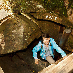 A young girl emerges from a cave at Lost River Gorge in New Hampshire's White Mountains. North Woodstock.