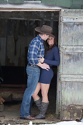 cowboy holding a girl in a barn doorway