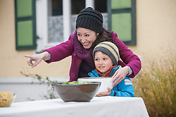 Mother assisting her son to keep the bowl on the table, Bavaria, Germany