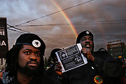 A full rainbow appears in the sky over two members of the New Black Panthers after hundreds marched from Magnuson Park to the Montlake Bridge, Tuesday, in honor of Charleena Lyles, who was fatally shot by police Sunday morning, June 20, 2017.