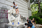 Elisabeth DeLeon, 27, of Sacramento, scrubs a statue that was defaced on Capitol Mall in downtown Sacramento on Sunday, May 31, 2020.