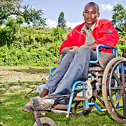 "Although disabled and wheelchair-bound, Robert Sang is a keen participant in village life and decision-making. Happily, being disabled has been increasingly de-stigmatised in recent years in Kenya, and ""disability is not inability"" is a well-used and widely understood phrase here. The programme has been designed such that everyone can participate; even the disabled, such as Robert, have an equal chance of holding youth leadership positions. In some areas, disabled people have even managed to succeed in becoming presidents of their groups. In Soba Location, Chief Tuwei proudly holds Robert up as an example. Nandi County, Rift Valley Province, Kenya."