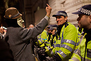 Protestor with Guy Fawkes mask on swearing at Police with Policeman smiling. Thousands of protesters, some masked meet in Trafalgar square and march around central London marking 5th November guy fawkes night, some inceidents were reported and scuffles with the Police in Parliament square, Buckingham palace, Regent Street, Picadilly and Oxford street, London, UK.