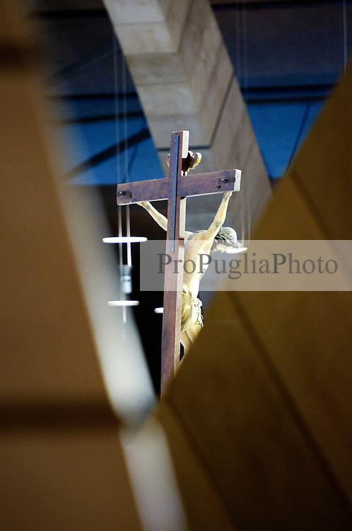 """È stata inaugurata il 1° luglio 2004, la nuova Chiesa di San Pio da Pietrelcina progettata dall'architetto Renzo Piano. Esattamente 45 anni prima, nel 1959,  veniva inaugurata la chiesa """"grande"""" di Santa Maria delle Grazie. .Sorta a fianco del santuario e convento in cui visse il frate, ha la forma di una conchiglia e la sua pianta ricorda quella della spriale archimedea. Enormi archi parto dal perimetro esterno e terminano nel fulcro della """"conchiglia"""" dove è posto l'altare. Possenti staffe d'acciaio, ancorate agli archi, sorreggono la volta che ricoperta di rame preossidato espone alla vista un intenso un colore verde-rame.   .Con i suoi 6000 mq, è la seconda chiesa più grande in Italia per dimensioni, dopo il Duomo di Milano. Può ospitare oltre 7000 persone e per la sua realizzazione sono state impiegati 30.000 metri cubi di calcestruzzo, 1.320 blocchi in pietra di Apricena, 70.000 metri cubi di scavo in roccia, 60.000 chili di acciaio, 500 mq di vetro, 19.500 mq di rame preossidato. Ogni anno è meta di oltre sei milioni di pellegrini..Nella foto la parte interna della chiesa con i suoi archi che si incrociano in un gioco di linee curve. Sullo sfondo il crocifisso sospeso al centro della chiesa."""