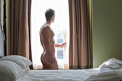 nude man standing by a window in a bedroom
