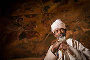 Ethiopian priest standing before a 17th century Wall painting in the Church of Abraha We Atsebeha. Ethiopia, Horn of Africa