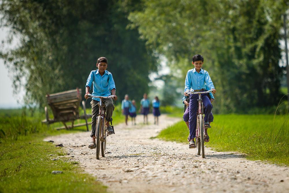 Schoolchildren cycling to school along a country lane, Sharanamati Village, Sharanamati, Nepal