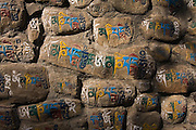 Colorfully painted Tibetan Buddhist mantras, or prayers in the rock walls at the base of Swayambhunath Temple, Kathmandu, Nepal.