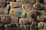 Colorfully painted Tibetan Buddhist mantras, or prayers in the rock walls at the base of Swayambhunath Temple, Kathmandu, Nepal.