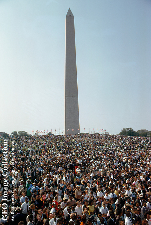 """A crowd of people on the Washington Monument grounds hold hands and sing during the """"March on Washington"""" in 1963. The people are of different races."""