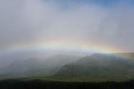 A rainbow arcs across green mountains in Katmai National Park, Alaska