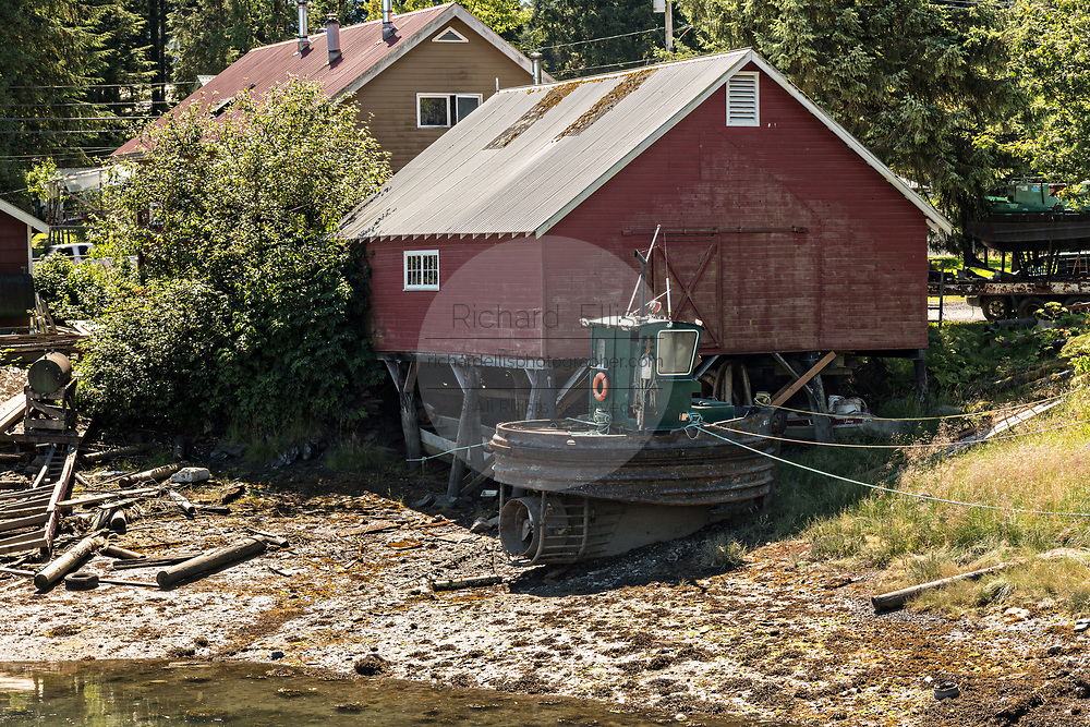 A mini tugboat tied up against an old wooden boathouse along Hammer Slough in Petersburg, Mitkof Island, Alaska. Petersburg settled by Norwegian immigrant Peter Buschmann is known as Little Norway due to the high percentage of people of Scandinavian origin.