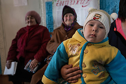18 month-year-old Danilo waits with his mother to see one of the MSF doctors at a mobile clinic set up in the village of Gorodishe near Lugansk.