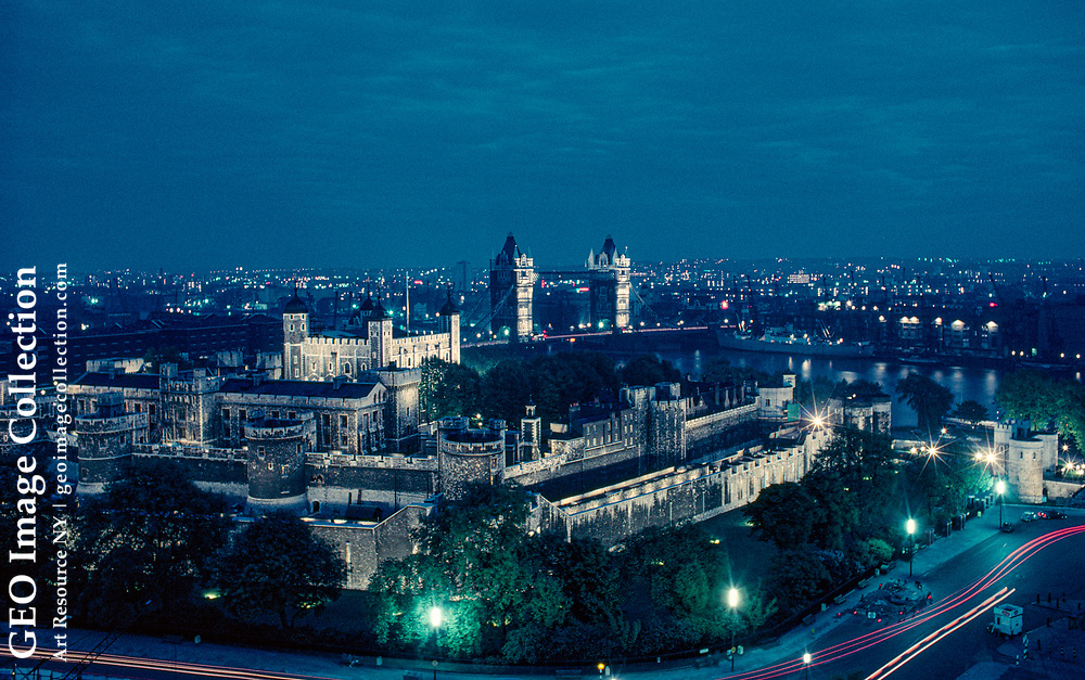 Crenellated walls of the Tower of London glow against city lights.