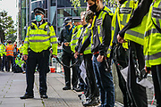 A police officer (L) is holding the end of a chain in which a group of 10 Extinction Rebellion activists chained themselves outside Home Office in Marsham Street, central London on Friday, Sept 4, 2020.<br /> Marsham street remains both ways closed by the police. There are other Extinction Rebellion protests ongoing in London. Environmental nonviolent activists group Extinction Rebellion enters its 4th day of continuous ten days protests to disrupt political institutions throughout peaceful actions swarming central London into a standoff, demanding that central government obeys and delivers Climate Emergency bill. (VXP Photo/ Vudi Xhymshiti)