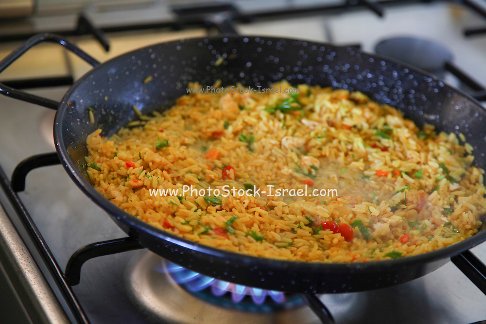 Paella, (Paeia) a Valencian rice dish cooking on a stove