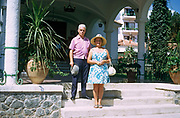 A middle-aged 70s husband and wife stand on hotel steps in the Spanish Mediterranean resort of Marbella on the Costa del Sol, southern Spain. Holding his trilby hat in one hand the husband stands slightly higher than his wife, in a more dominant stance than his lady companion. The woman wears a floppy holiday hat in the bright sunshine before an excursion elsewhere.