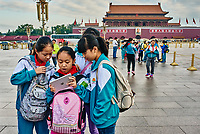Beijing , China - September 24, 2014: Chinese children holding ipad digital tablet in front of  forbidden city Tiananmen Square  Beijing China