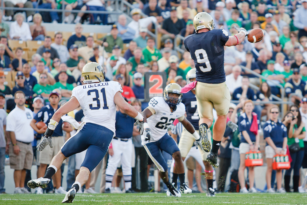 Notre Dame tight end Kyle Rudolph (#9) attempts to make leaping catch surrounded by Pittsburgh defensive back Dom DeCicco (#31) and defensive back Antwuan Reed (#22) during NCAA football game between Pittsburgh and Notre Dame.  The Notre Dame Fighting Irish defeated the Pittsburgh Panthers 23-17 in game at Notre Dame Stadium in South Bend, Indiana.
