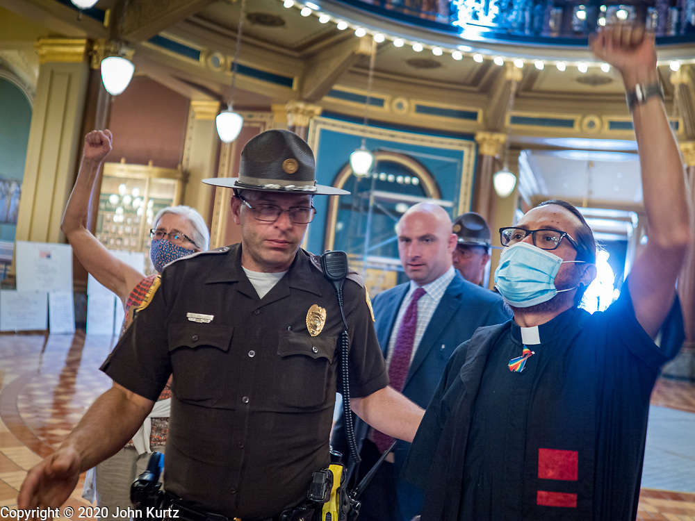 12 JUNE 2020 - DES MOINES, IOWA: An Iowa State Trooper leads a member of the Governor's staff through Black Lives Matter supporters participating in a protest in the rotunda of the Iowa capitol. About 75 activists from Black Lives Matter came to the Iowa State Capitol in Des Moines Friday to talk to Iowa Governor Kim Reynolds. They've been trying to meet with Gov. Reynolds all week. She made time for them Friday and met with 5 representatives of the organization without any media in the room. They wanted to talk to her about police violence against African-Americans and racial disparities in Iowa's justice system. While the 5 met with the Governor, the remaining activists picketed the hall in front of her office and chanted.    PHOTO BY JACK KURTZ