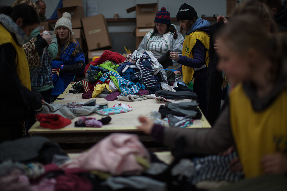 A group of volunteers from across Europe sorting donations of clothing for people at the camp in Calais known as The Jungle. The Jungle houses some 7000 people in temporary accommodation, mainly tents. There is no official support for the camp, but people arriving there are supported by networks of volunteers with donated food, clothing and medical aid.