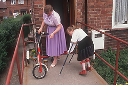 Mother and young girl with disability wearing leg braces and using walking sticks,