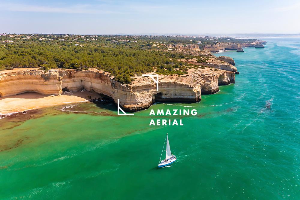 Aerial view of a sailboat cruising by the beach of Praia da Corredoura on the coastal cliffs of Lagoa, Algarve, Portugal.