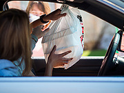 "26 APRIL 2020 - JEWELL, IOWA: A motorist in Jewell brings a sack of ""grab and go"" roast pork dinners into her car in Jewell Sunday. Jewell, a small community in central Iowa, became a food desert when the only grocery store in town closed in 2019. It served four communities within a 20 mile radius of Jewell. Some of the town's residents are trying to reopen the store, they are selling shares to form a co-op, and they hold regular fund raisers. Sunday, they served 550 ""grab and go"" pork roast dinners. They charged a free will donation for the dinners. Despite the state wide restriction on large gatherings because of the COVID-19 pandemic, the event drew hundreds of people, who stayed in their cars while volunteers wearing masks collected money and brought food out to them. Organizers say they've raised about $180,000 of their $225,000 goal and they hope to open the new grocery store before summer.           PHOTO BY JACK KURTZ"