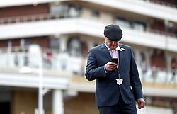 A racegoer checks his phone during for Champion Day of the 2018 Cheltenham Festival at Cheltenham Racecourse.