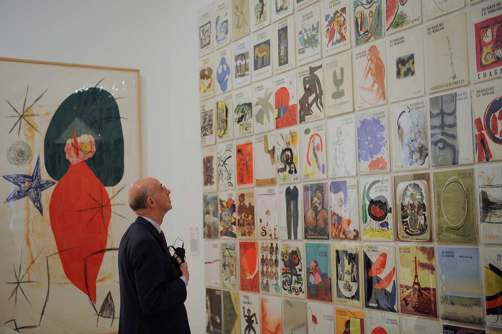London.  September 30, 2008.  A museum goer admires a wall sized collage of Derriere Le Miroir covers from 1946-82, part of the Miro, Calder, Giacometti, Braque exhibition at the Royal Academy of Arts.  The show opens on October 4 and runs until January 2, 2009.