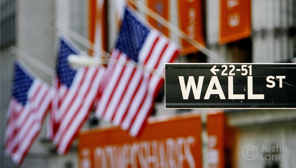 A sign for Wall Street is seen with the flags of the New York Stock Exchange in the background in New York, New York on Wednesday 28 February 2007. The Dow Jones Industrial average ended down 416 points yesterday, but stocks showed some signs of rebounding on Wednesday.