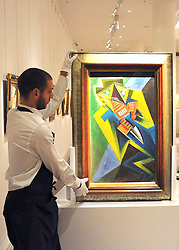 © licensed to London News Pictures. LONDON, UK.  09/06/11. An assistant holds a double sided painting by Josef Capek called Sailor and Phantomas estimated to be worth £150,000- 200,000.  Press preview for Sotheby's upcoming Sale of The Hascoe Family Collection of Important Czech Art. Highlights include a group of 20 paintings from Frantisek Kupka, including Movement, which is estimated to fetch £500,000 to £700,000 and Bohumil Kubi?ta's Still Life with Fruit of 1909, estimated at £300,000 to £500,000.  Photo credit should read Stephen Simpson/LNP