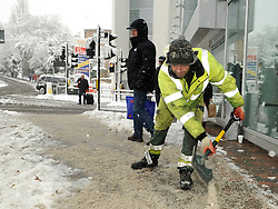 © under license to London News Pictures. 1.12.2010 Snow chaos in Orpington in Kent.  Council worker gritting outside Tesco in Orpington.. Picture credit should read Grant Falvey/London News Pictures