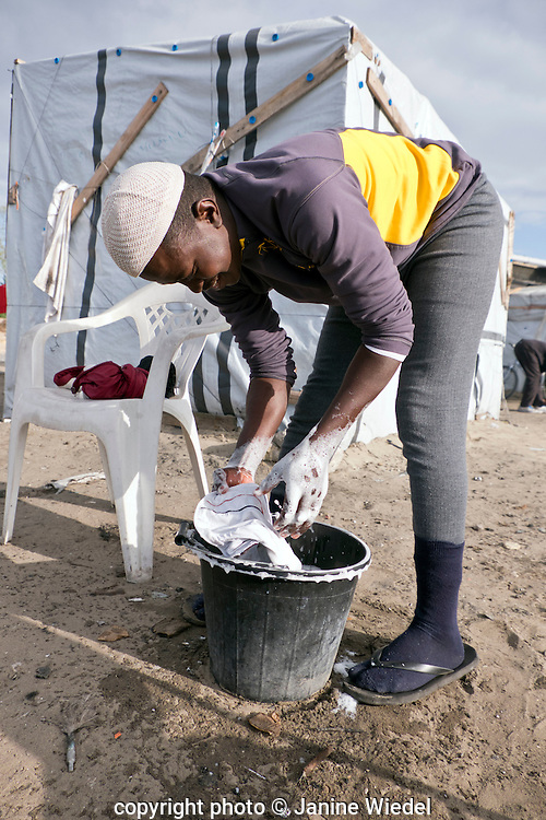 Young Ethiopian man doing his laundry in a bucket at the Calais Jungle Refugee and Migrant Camp in France