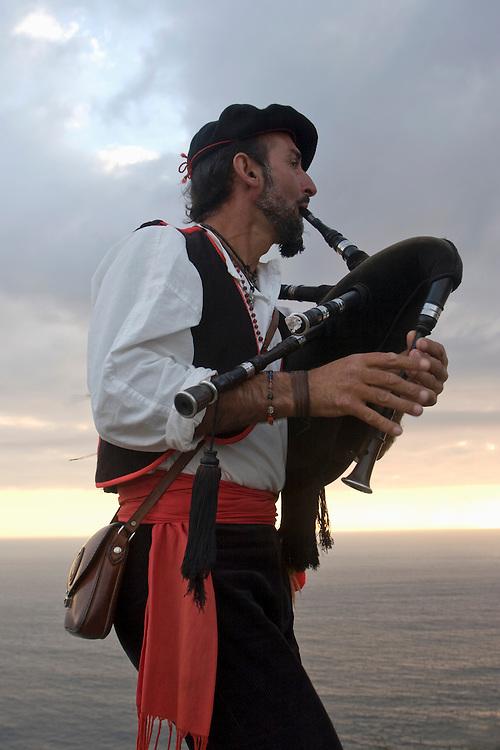 Costa de Morte. Un gaiteiro toca la gaita al atardecer en Cabo Finisterre, considerado el punto final del Camino de Santiago.