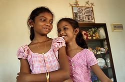 Right to left, Sisters Shrianna and Brianna Barthelot, 11 and 13, joke inside the apartment they are now residing in with relatives, Batticaloa, Sri Lanka, July 10, 2005. The sisters lost both parents and their older brother in the tsunami. More than 150 members in this community of less than 1000 people died in the tragic event.