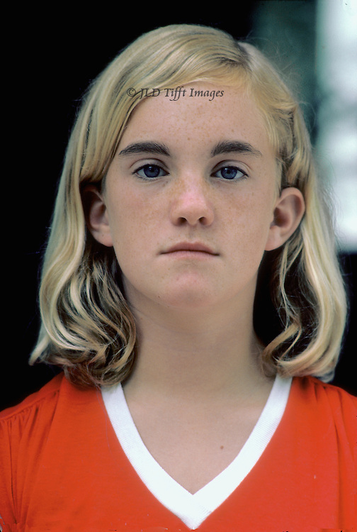 Head shot, frontal, solemn even aggressive facial expression.  Smooth blonde hair curling to her shoulders.  Wearing red shirt.