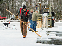 David White lines up ice blocks into the canal for loading on Wednesday morning during the annual ice harvest with the Rockywold-Deephaven Camp crew at Squaw Cove on Squam Lake.  (Karen Bobotas/for the Laconia Daily Sun)