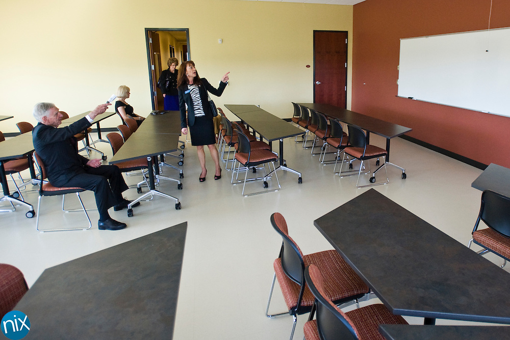 Dole Food Company Inc. owner David Murdock, left, tries out a classroom chair during a tour from Dr. Marcy Corjay, of Rowan-Cabarrus Community College, of the college's new building at the North Carolina Research Center in Kannapolis Thursday morning.  (Photo by James Nix)