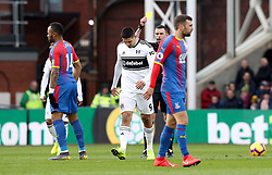 Crystal Palace's Jordan Ayew (left) receives a yellow card from Referee Michael Oliver during the Premier League match at Selhurst Park, London.