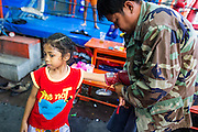 23 DECEMBER 2014 - BANGKOK, THAILAND: A man helps BAI THONG, 7 years old, put her gloves on before she climbed into the ring at the Kanisorn gym in Bangkok. She has been boxing for about 5 months. The Kanisorn boxing gym is a small gym along the Wong Wian Yai - Samut Sakhon train tracks. Young people from the nearby communities come to the gym to learn Thai boxing. Muay Thai (Muai Thai) is a mixed martial art developed in Thailand. Muay Thai became widespread internationally in the twentieth century, when Thai boxers defeated other well known boxers. A professional league is governed by the World Muay Thai Council. Muay Thai is frequently seen as a way out of poverty for young Thais. Muay Thai professionals and champions are often celebrities in Thailand.     PHOTO BY JACK KURTZ