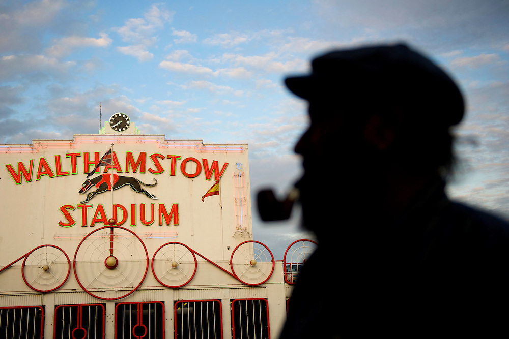"""Lifelong Walthamstow resident Jeff Harris, 65, admires the famous stadium at dusk, on the final night of racing in its 75 year history.  """"What a shame and loss for the heritage of England,"""" Harris said.  Forced to close as a result of diminishing profits and poor attendance, record crowds flocked to take in the festivites one last time.  ."""