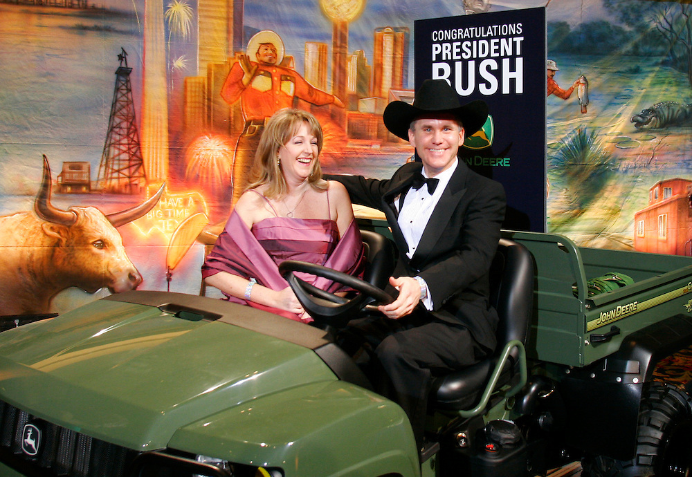 A look-alike for President George W. Bush David Cline (R) and his wife Jennifer of Wilmington, DE pose in a John Deere utility vehicle at the Black Tie and Boots inaugural ball in Washington January 19, 2005. The ATV was one of the prizes to be given away at the ball in advance of Bush's inauguration January 20th.   REUTERS/Rick Wilking