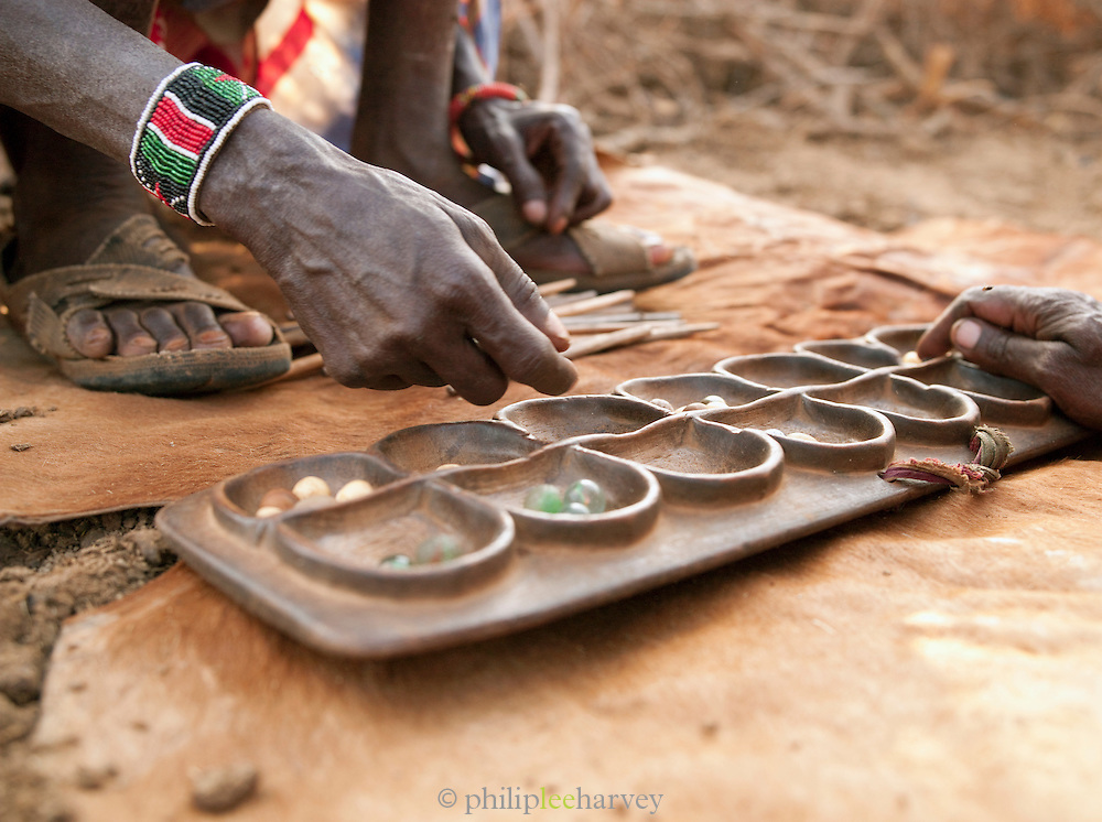 """Maasai tribesmen playing the game Bao, a type of Mancala (""""count and capture"""") Board game commonly played in east Africa. Tipilit village near Amboseli National Park, Kenya"""