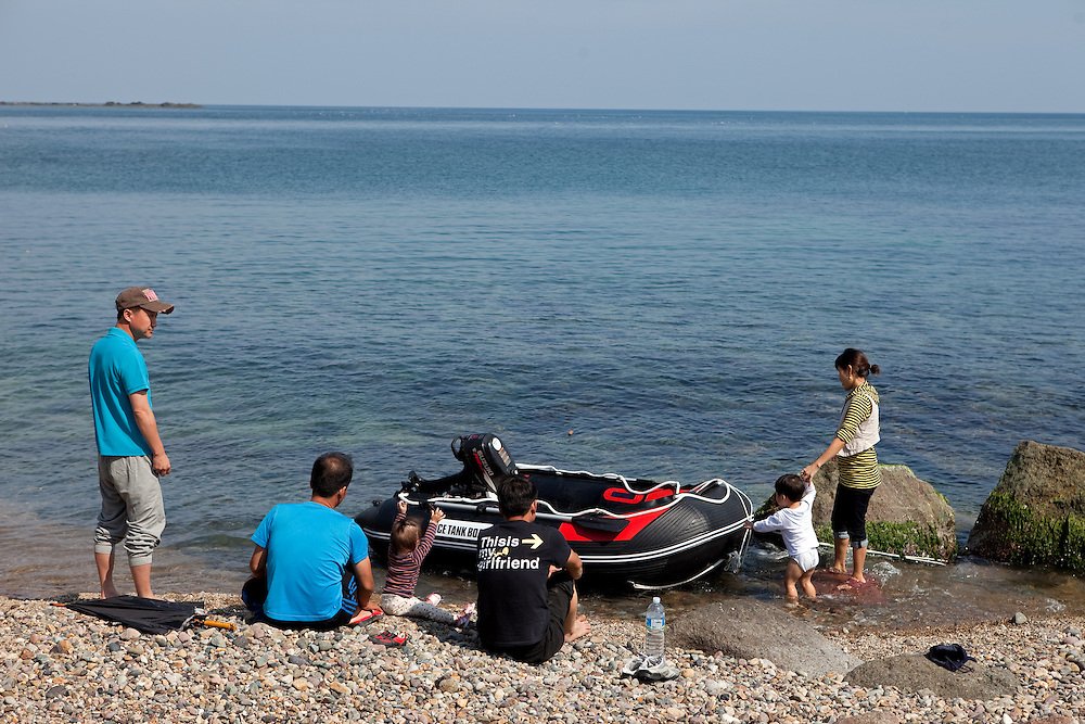 Korean people with children and rubber dinghy spending free time on the coast / South Korea, Republic of Korea, KOR, 04 October 2009: