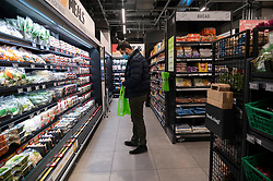 © Licensed to London News Pictures. 04/03/2021. London, UK. A customer is seen shopping inside the first AMAZON GO grocery store in the UK opens in Ealing, West London. Shoppers need to use app to shop inside the store and pick up groceries without stopping to pay. Photo credit: London News Pictures