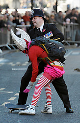 © Licensed to London News Pictures. 11/11/2012. Bristol, UK. A person on a skateboard rode past the military parade after the ceremony and was caught and led away by police, at Remembrance Sunday in Bristol City Centre.  11 November 2012..Photo credit : Simon Chapman/LNP