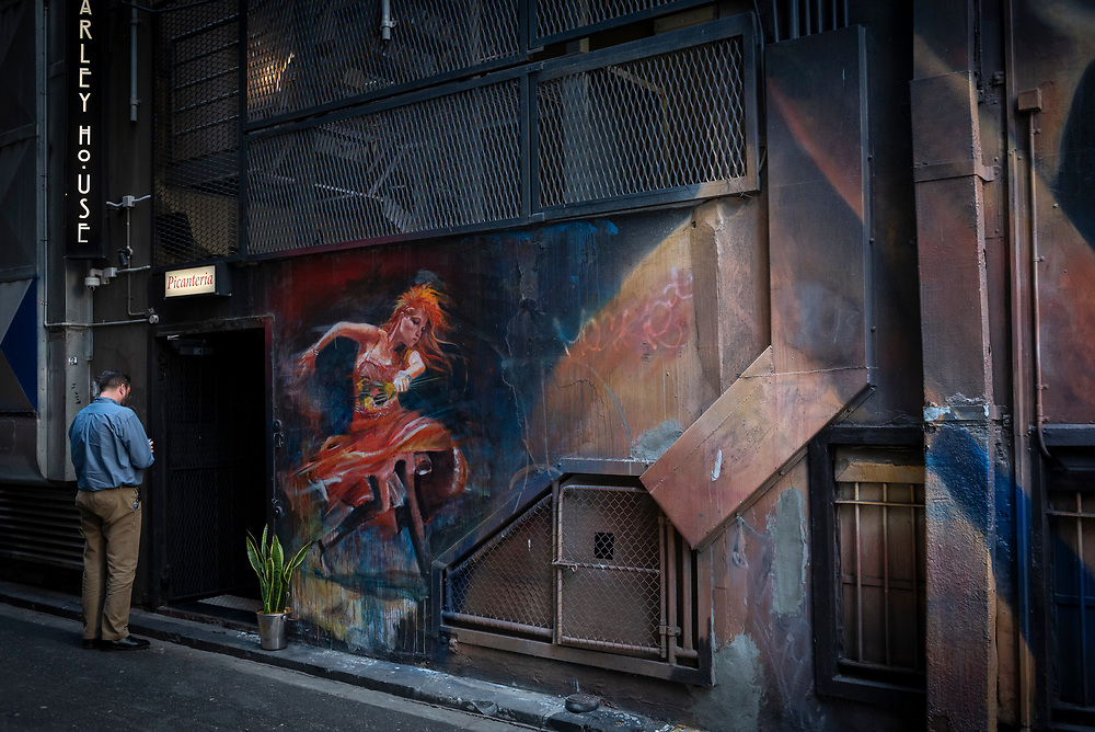 Melbourne, Australia - September 1, 2017: A man stands near a mural of Cyndi Lauper, painted by Vincent Fantauzzo as a tribute when her stage musical 'Kinky Boots' opened in Melbourne in 2016.