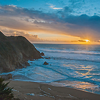 A sunset glows over the Pacific Ocean and Gray Whale Cove State Beach near Montara, California.